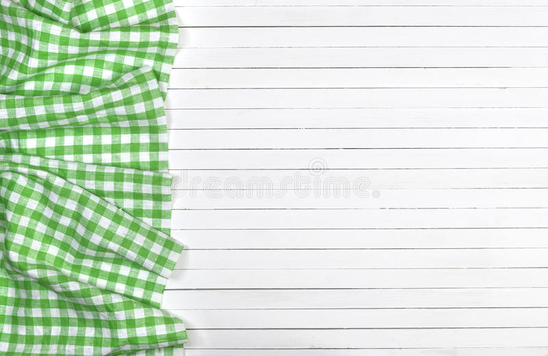 Green checkered tablecloth on wooden table, top view. Green checkered tablecloth on a light wooden table, top view royalty free stock image