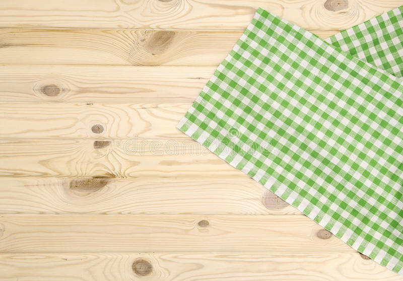 Green checkered tablecloth on wooden table. Green checkered tablecloth vor texture or background stock photo