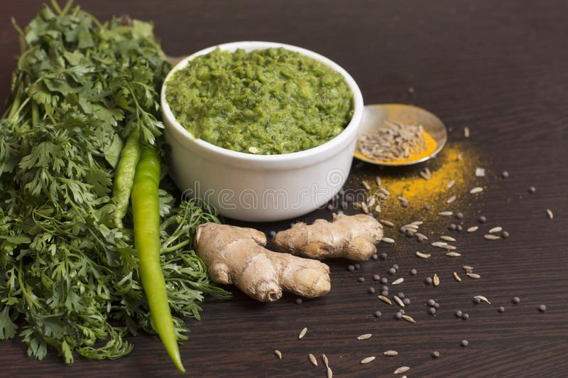 Green chili thecha or chutney with ingredients served in a bowl stock images