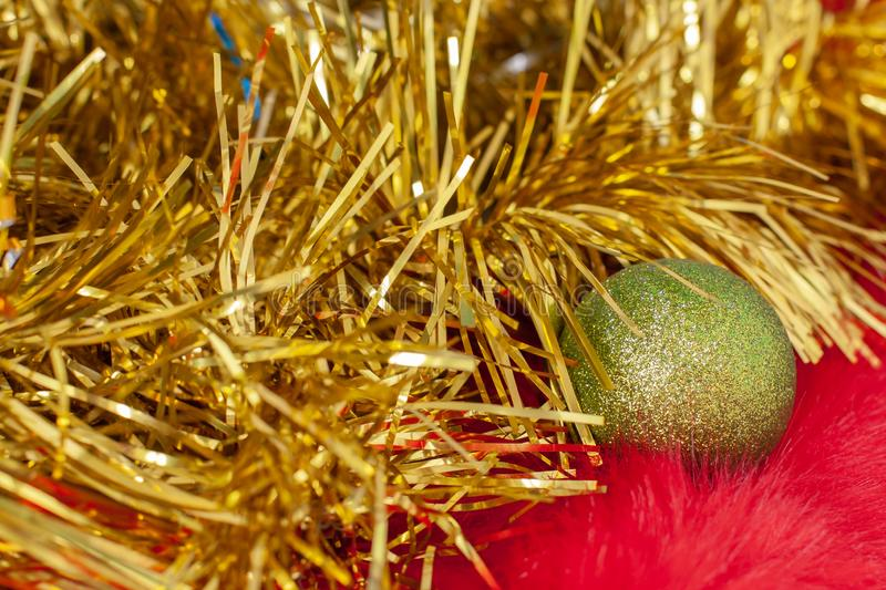 Green Christmas ball on red fur and Christmas golden tinsel. Tinsel is like a Christmas tree branch. Fluffy red fur with a long pile. Selective focus on the royalty free stock images