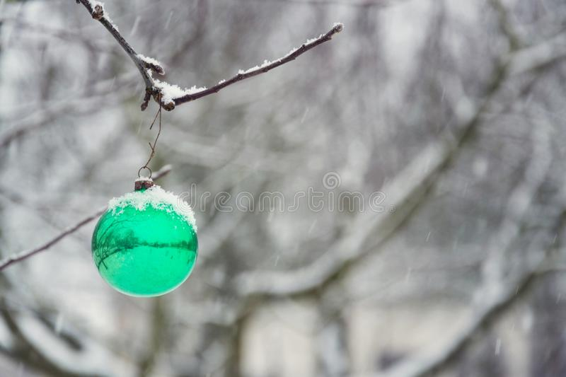 Green Christmas ball vintage glass decoration hanging on tree outdoors, falling snow winter landscape royalty free stock photography