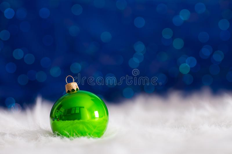 Green Christmas ball on white fur with garland lights on blue bo. Keh background. New year card with empty space. Xmas festive decoration stock photos