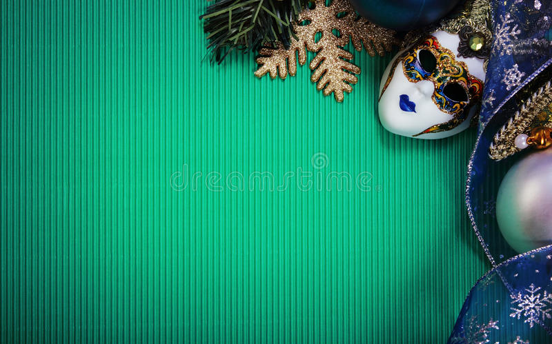 Green christmas card with carnaval mask stock photo