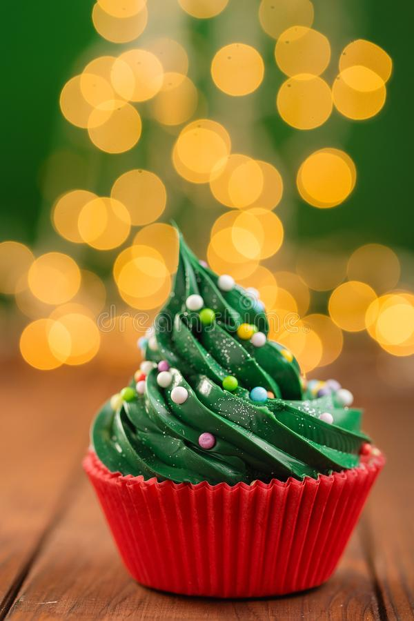 Green christmas cupcake with bokeh on background. Green christmas cupcake with colorful sprinkles in red cup on wooden background with garland lights bokeh stock images