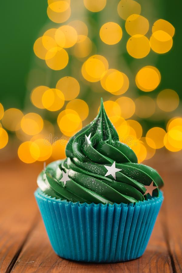 Green christmas cupcake with bokeh on background. Green christmas cupcake with stars sprinkles in blue cup on wooden background with garland lights bokeh royalty free stock photography