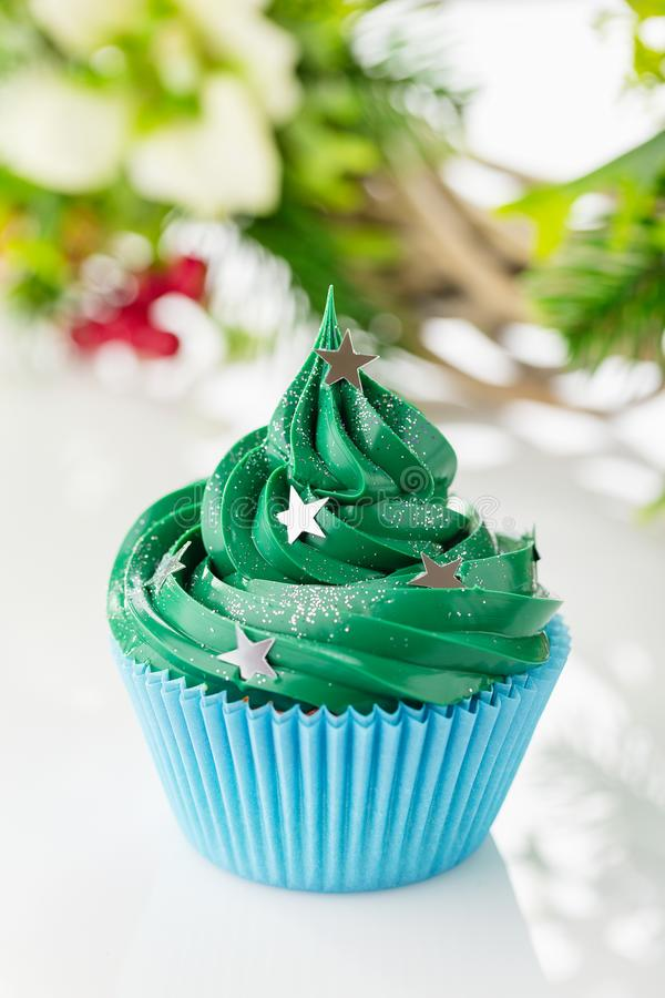 Green christmas cupcake with festive decorations. Christmas green cupcake with star sprinkles in blue cup on white background with festive decorations stock photos