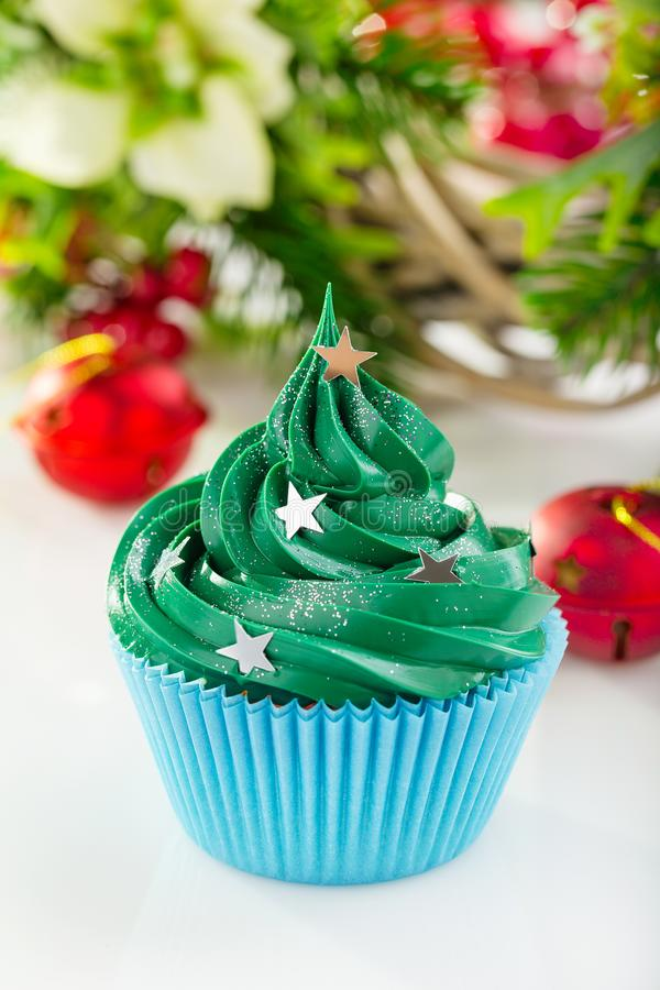 Green christmas cupcake with festive decorations. Christmas green cupcake with star sprinkles in blue cup on white background with festive decorations stock image