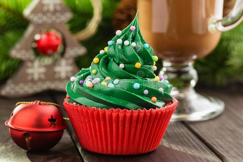 Green christmas cupcake in red cup. Christmas green cupcake with colorful sprinkles in red cup on wooden background with festive decorations and cup of cocoa royalty free stock image