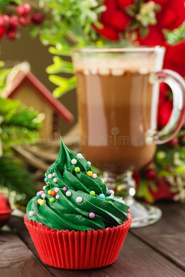 Green christmas cupcake in red cup. Christmas green cupcake with colorful sprinkles in red cup on wooden background with festive decorations and cup of cocoa stock photography