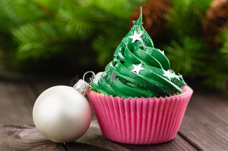 Green christmas cupcake with festive decorations. Green christmas cupcake with stars sprinkles in pink cup on wooden background with festive decorations royalty free stock photo