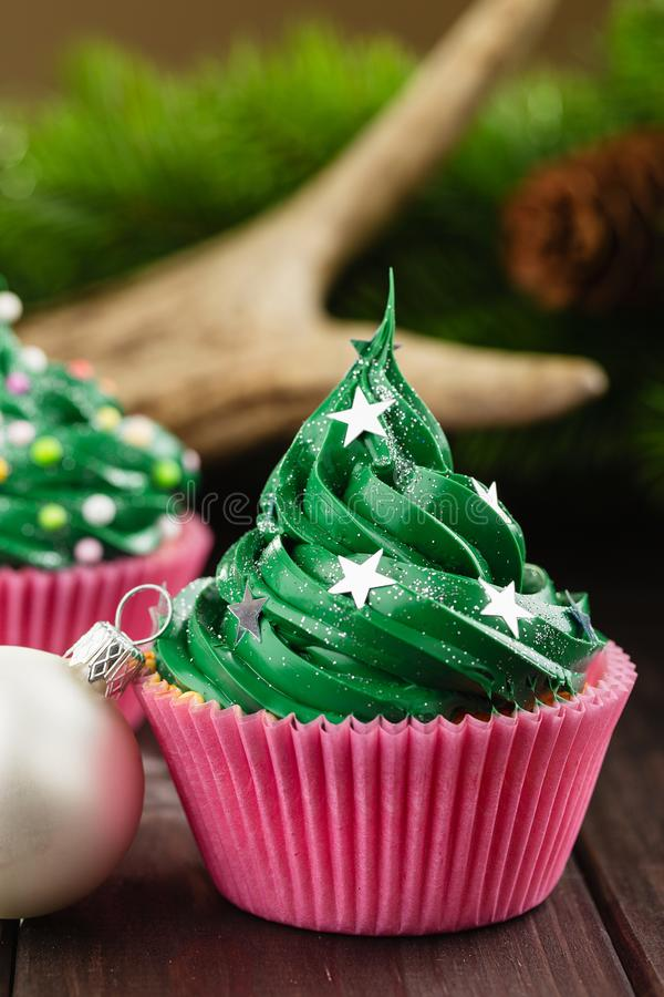 Green christmas cupcake with festive decorations. Green christmas cupcake with stars sprinkles in pink cup on wooden background with festive decorations royalty free stock images