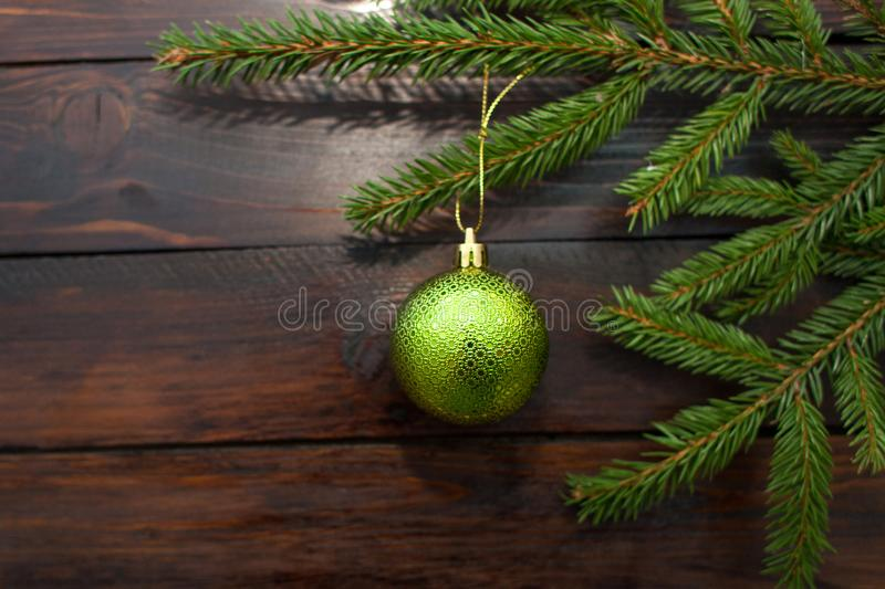 Green Christmas tree branches on a dark wooden background. New Year background with a green glass ball. Top view stock image