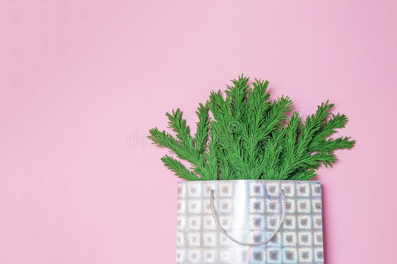 Green Christmas tree branches in a gift bag on the pink background flat lay, top view. Handmade New Year decor with copy space, stock photos