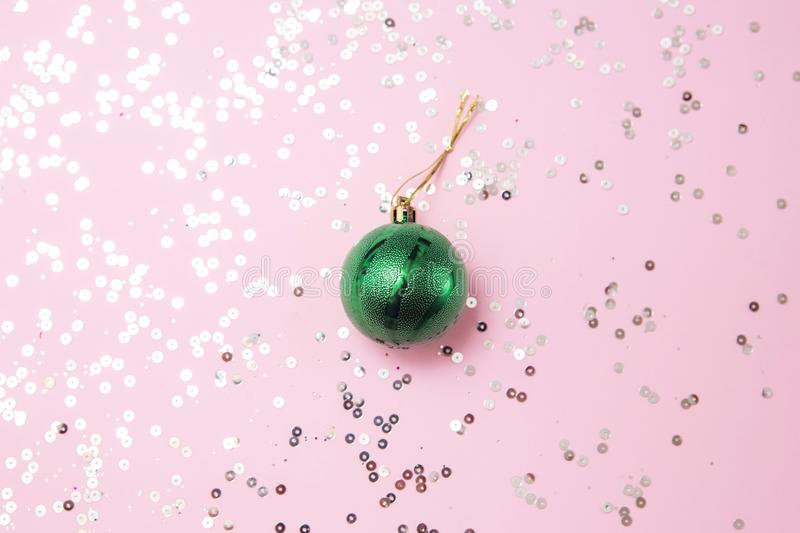Green Christmas tree toy on the pink background with glitters flat lay. New Year, Christmas, winter, minimalism, celebration stock photography