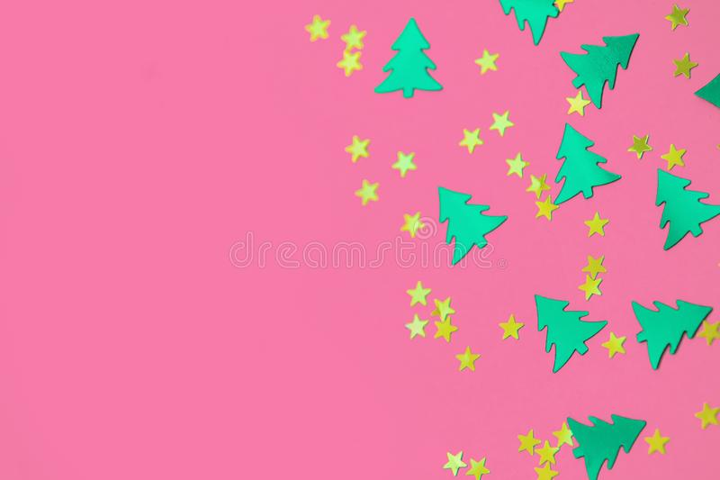 Green christmas trees and gold stars confetti sparse on pink background. Green metallic foil christmas trees and gold stars confetti sparse on pink background royalty free stock images