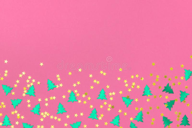 Green christmas trees and gold stars confetti sparse on pink background. Green metallic foil christmas trees and gold stars confetti sparse on pink background stock image