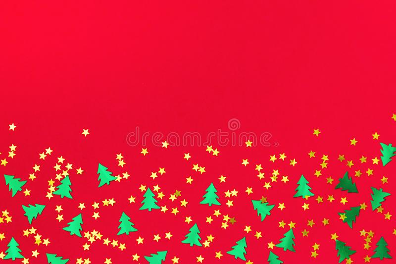 Green christmas trees and gold stars confetti sparse on red back. Green metallic foil christmas trees and gold stars confetti sparse on red background. Simple royalty free illustration