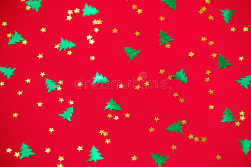 Green christmas trees and gold stars confetti sparse on red background. Green metallic foil christmas trees and gold stars confetti sparse on red background stock images