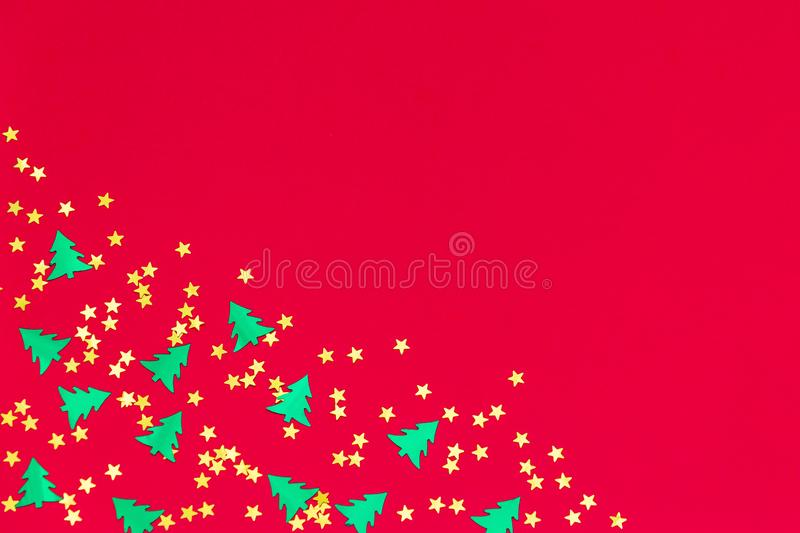Green christmas trees and gold stars confetti sparse on red background. Green metallic foil christmas trees and gold stars confetti sparse on red background stock illustration
