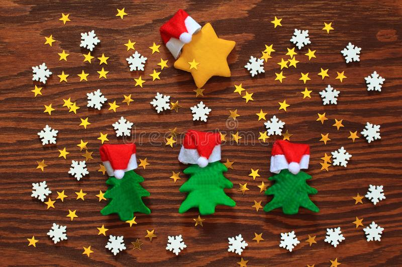 Green Christmas trees and a yellow star, in Santa hats. white snowflakes and yellow little stars. Christmas and new year holiday stock photos