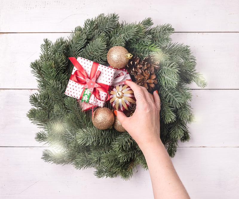 Green Christmas Wreath with Decorations on White Wooden Background Christmas Card Christmas Gift Box Top View Flat Lay Female Hand stock images