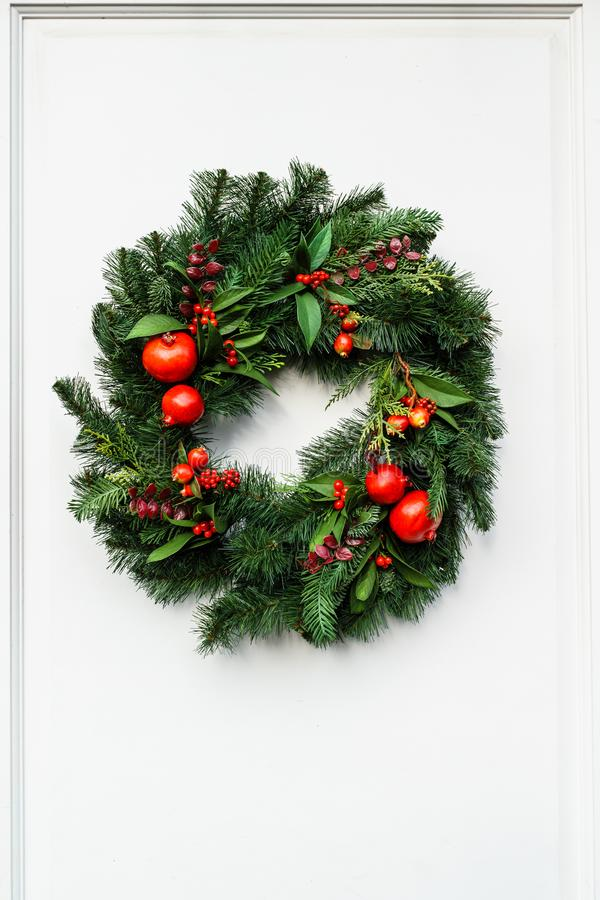Free Green Christmas Wreath With Pomegranate And Red Berries On White Door. Stock Photo - 108191230