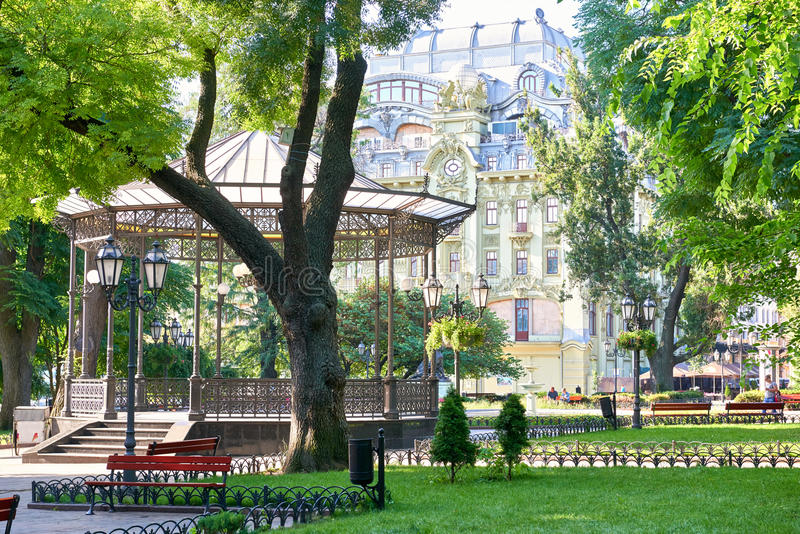 Green city park at center town, summer season, bright sunlight and shadows, beautiful landscape, home and people on street stock photo