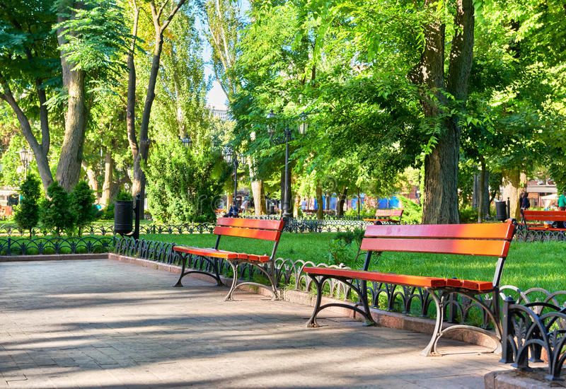 Green city park, summer season, bright sunlight and shadows, beautiful landscape, home and people on street stock photos