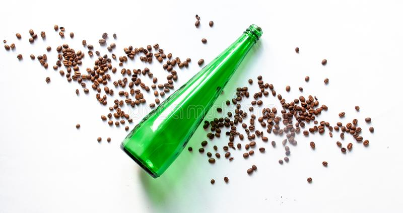 Green clean bottle and coffee beans on a white background. royalty free stock image