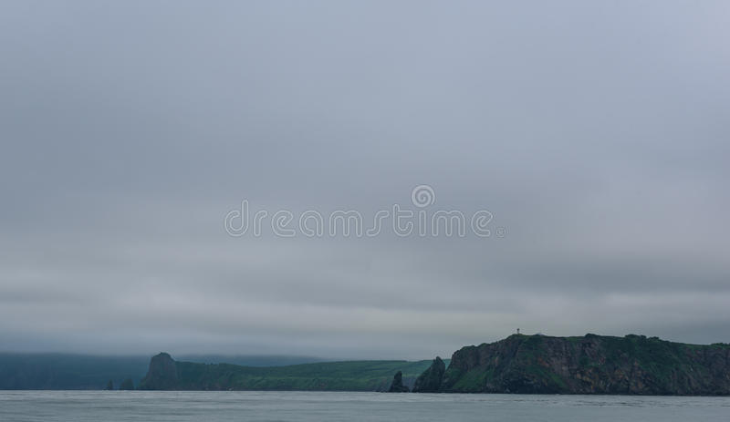 Green cliffs forming the coastline of the Avacha Bay. Kamchatka, Russia stock images
