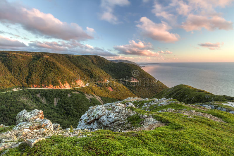 Green Cliffs Overlooking Cabot Trail. The winding Cabot Trail road seen from high above on the Skyline Trail at sunset in Cape Breton Highlands National Park royalty free stock photos