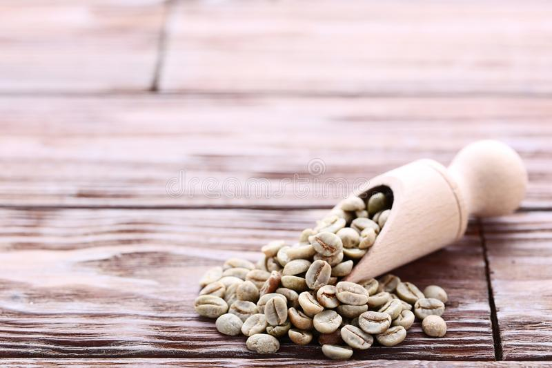 Green coffee beans. In scoop on brown wooden table royalty free stock images