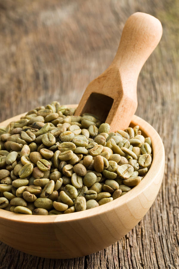 Green coffee beans in wooden bowl. Green coffee beans with wooden scoop in wooden bowl stock photos