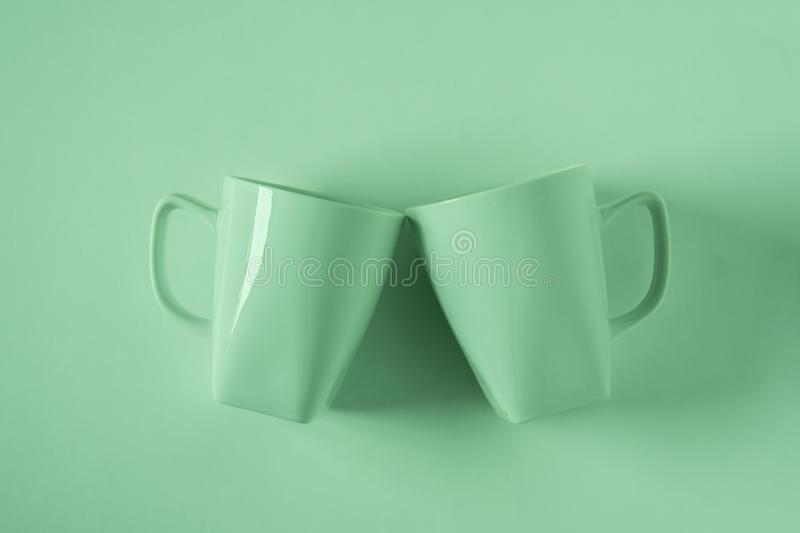Green coffee mugs on green background clinking in cheers with empty copyspace stock image