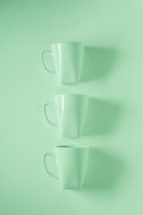 3 green coffee mugs on green background in a vertical row with empty copyspace royalty free stock photography