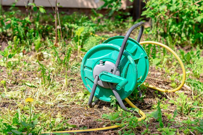 Green coil for watering with yellow hose on the lawn on a Sunny day royalty free stock image
