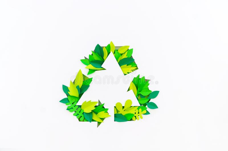 Green color recycling sign made from paper leaves. Cut tropics plant royalty free stock photos