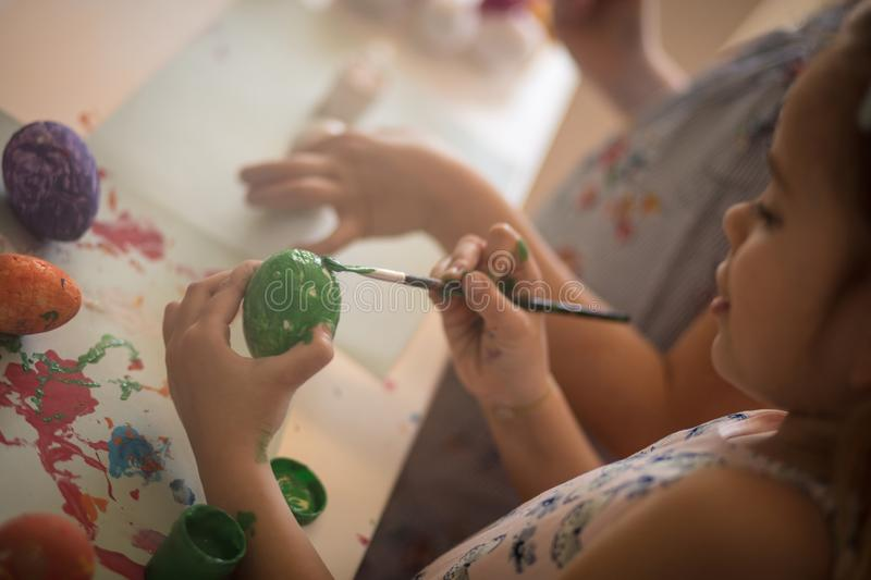 Green color is a sign for the spring and for the arrival of the Easter. Little girls coloring Easter egg royalty free stock photos