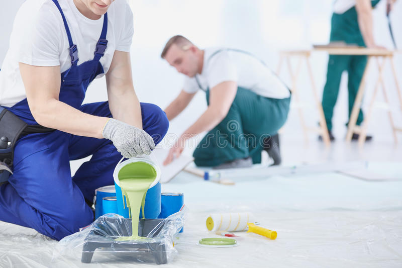 Green color to paint. Professional interior construction worker pouring green color to paint royalty free stock image
