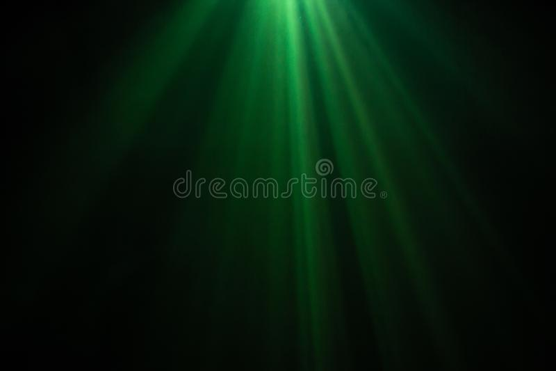 Green color wide lens projector with light beam for movie and cinema at night . smoke texture spotlight . black background royalty free stock photography
