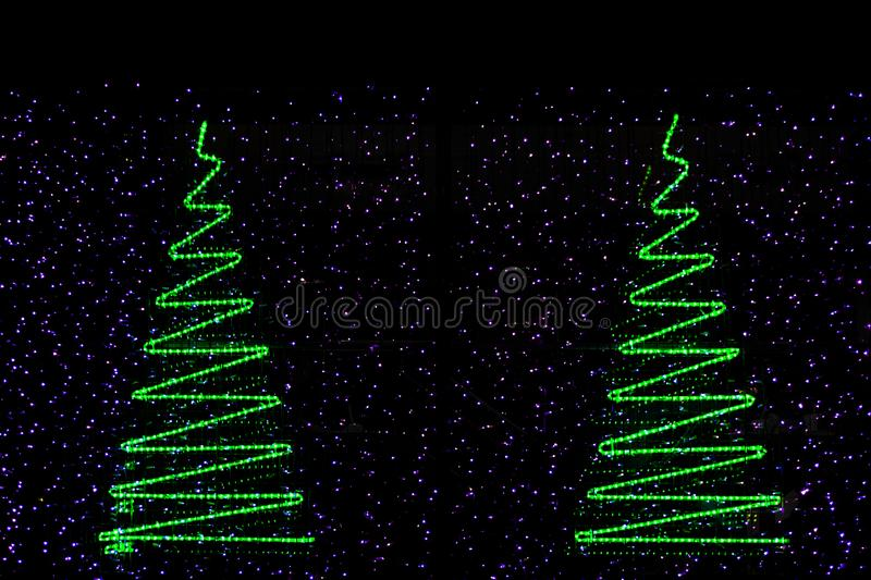 Green and colorful christmas tree lights against black background. The lights are beautifully decorated in shape of christmas xmas trees royalty free stock photos