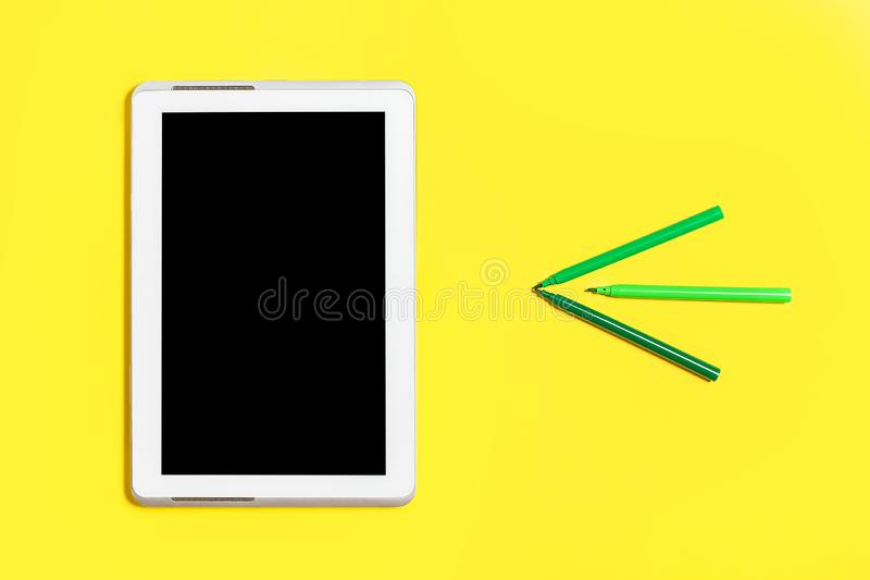 Green coloured chancery and a tablet pc on a yellow surface stock image