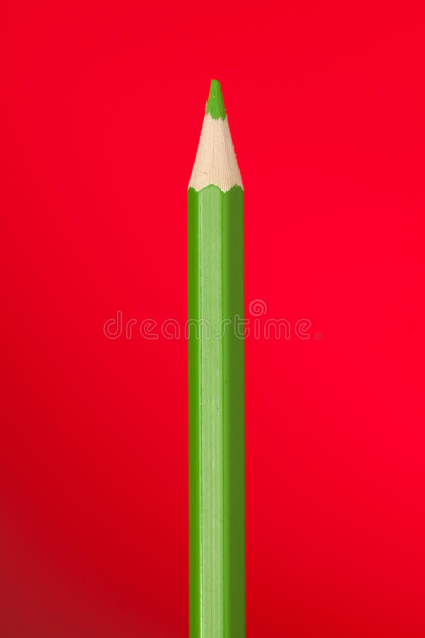 Green colouring crayon pencil isolated on red background. stock image