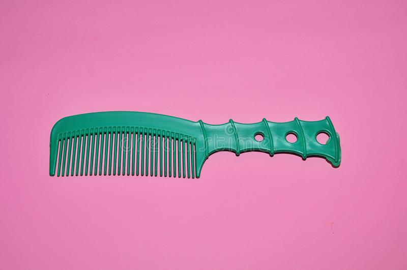 Green comb isolated on pink background stock photo