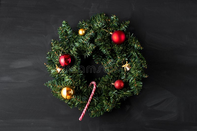 Green coniferous Christmas wreath decorated with red and yellow Christmas balls with bells and one candy can in the center on a bl royalty free stock images