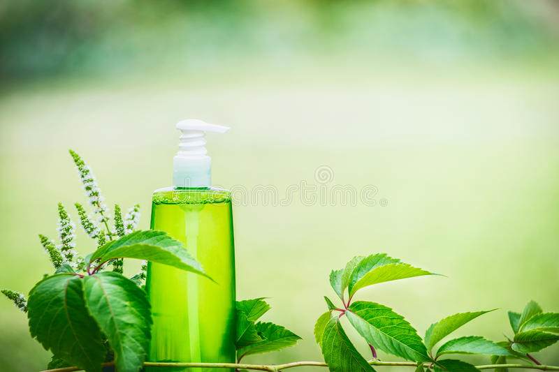 Green cosmetic product bottle for skin, body or hair care with green leaves at green nature background, front view. Natural cosmet. Ic concept, copy space stock photos