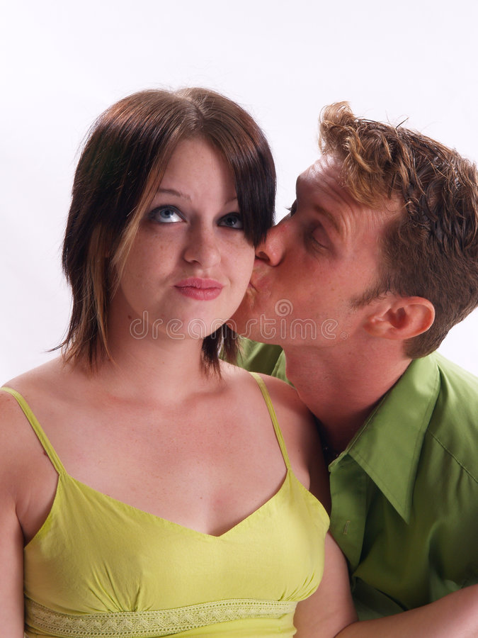 Guy kissing a girl on the cheek stock photo