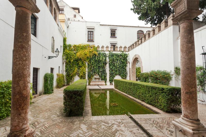 Green courtyard of Alcazar, example of Mudejar architecture of the 14th century, historical royal palace. SEVILLE, SPAIN - NOV 15: Green courtyard of Alcazar royalty free stock photography