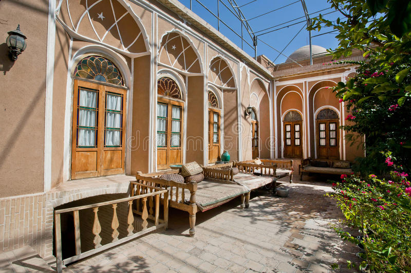 Green courtyard of beautiful iranian mansion with Ottoman beds. YAZD, IRAN: Green courtyard of beautiful iranian mansion with Ottoman beds for relaxation. With royalty free stock images