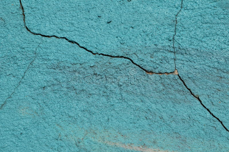 Cracked painted cyan wall. Large crack in the plastered concrete wall airbrushed with cyan graffiti paint stock image